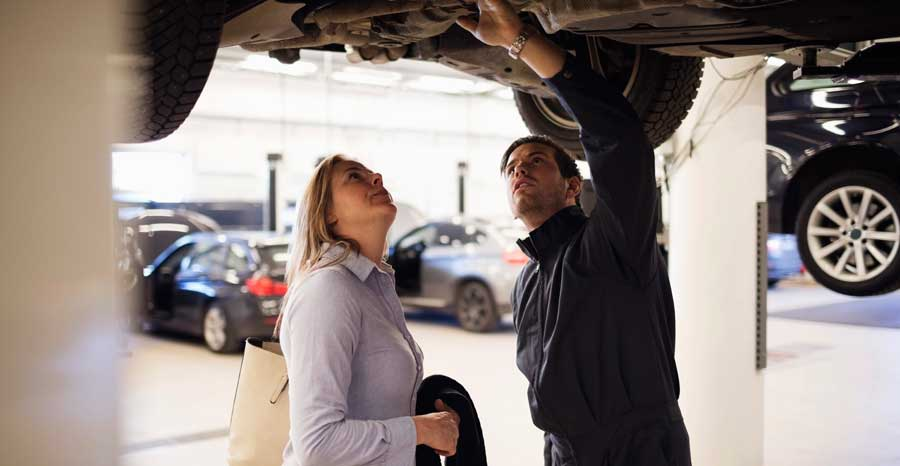 Mechanic showing an issue to a car owner